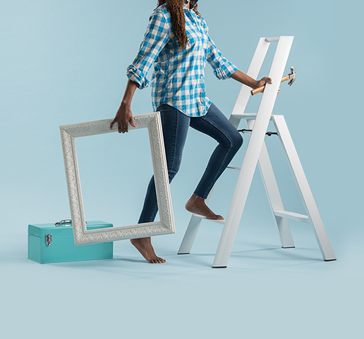 Artistic imagery of woman climbing up a ladder, holding a picture frame