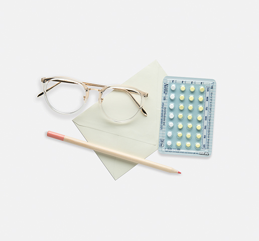 glasses, paper, contraceptives and a pencil on a desk
